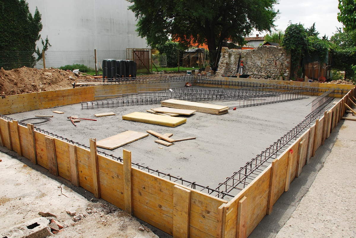 A house foundation site with steel reinforcement cages surrounded by wooden shuttering The cages are in the process of being laid out before the concrete is poured. Radon Iglus can be seen in the background